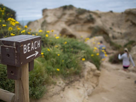 Hikers make their way down the trail to the beach at