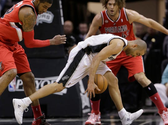 San Antonio Spurs' Tony Parker, center, works the ball around Portland Trail Blazers' LaMarcus Aldridge (12) and Robin Lopez, right, during the first half of Game 5 of a Western Conference semifinal NBA basketball playoff series, Wednesday, May 14, 2014, in San Antonio. (AP Photo/Eric Gay)