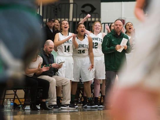 Carter players celebrate a basket during a high school