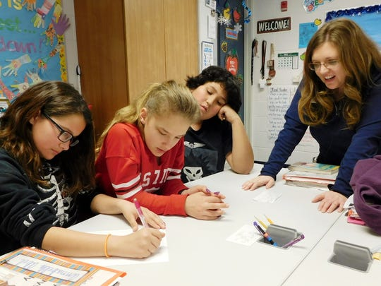 Angie Polter, right, assists students in writing instructions