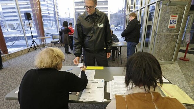 Jim Leissner of Milwaukee shows his photo ID to election inspectors Judy Harmon (left) and Tarubia King before voting at the Frank P. Zeidler Municipal Building in the Feb. 16 primary.