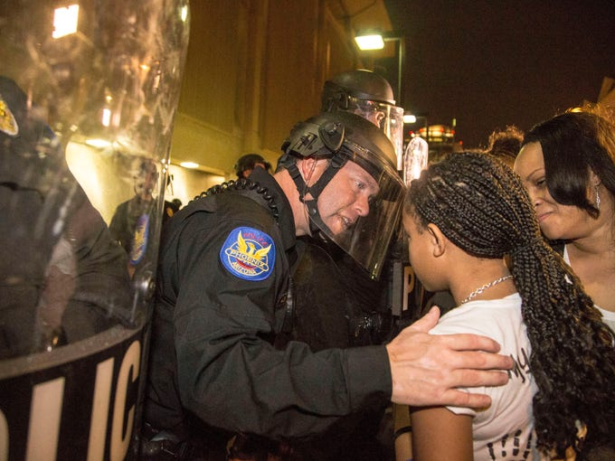 A Phoenix police officer clad in riot gear shakes the