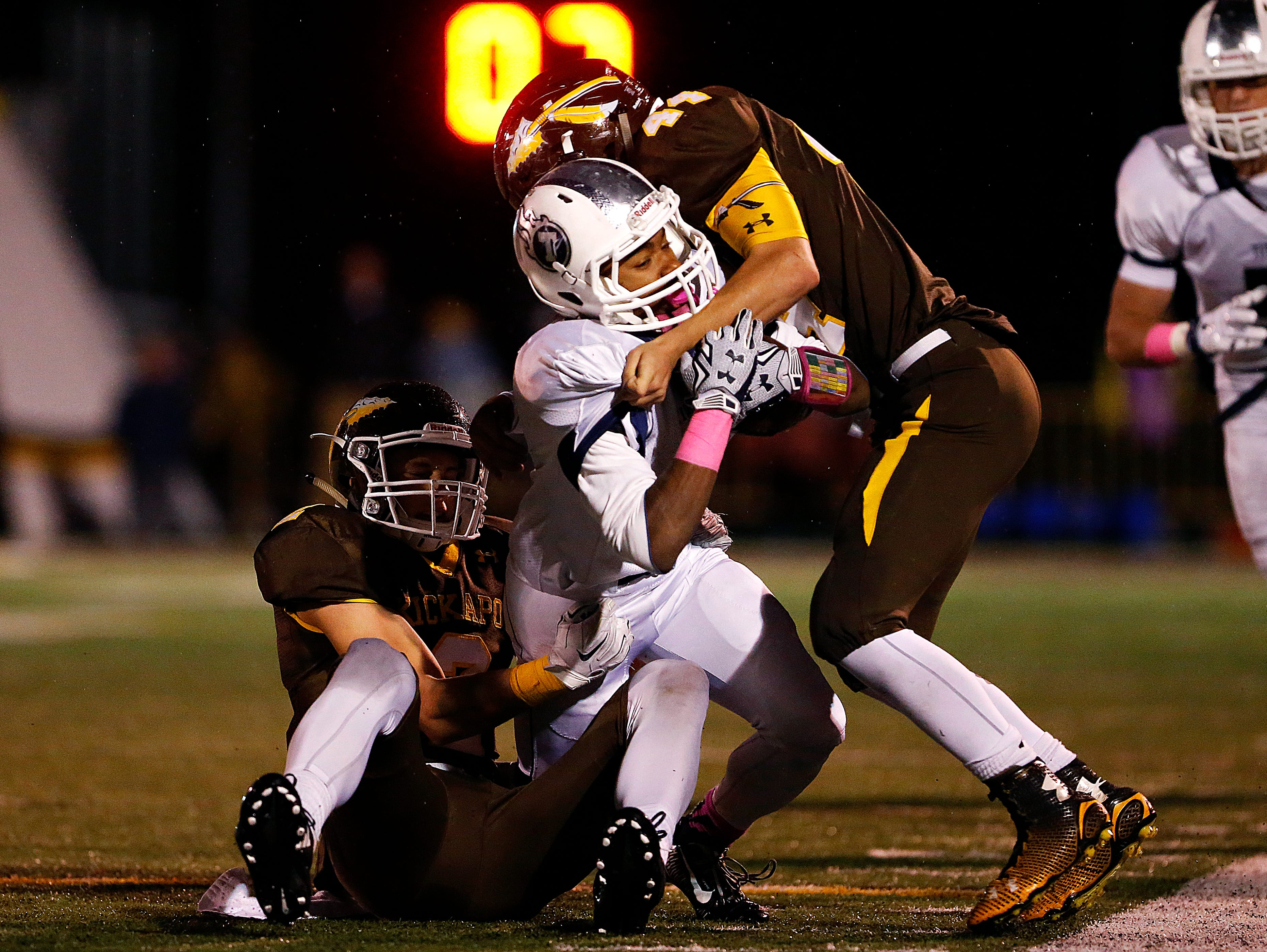Lee's Summit West High School wide receiver Mario Goodrich (4) is tackled by Chiefs defenders Travis Vokolek (2) and Tre Woodring (44) during second quarter action of the Titans' game against Lee's Summit West High School at Pottenger Stadium in Springfield, Mo. on Oct. 30, 2015. Kickapoo won the game 26-7.