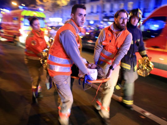 A woman is evacuated from the Bataclan theater after a shooting in Paris.