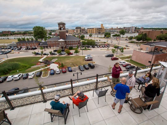 Patrons enjoy their drinks with a view on the patio at Titletown Roof Tap, part of Titletown Brewing Co., in Green Bay.