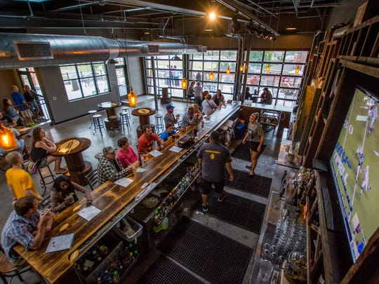 Patrons enjoy their drinks inside Titletown Roof Tap, part of Titletown Brewing Co., in Green Bay in August.