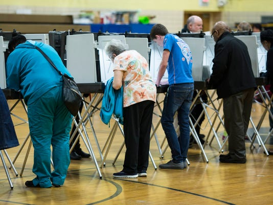Voters cast their ballots at a voting precinct on Election Day in Flint, Mich.
