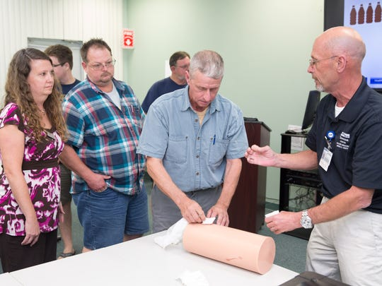 David Schmitt, right, Health First's Training Center manager, teaches the techniques to control bleeding to participants in Health First's Training Center Stop the Bleed class.