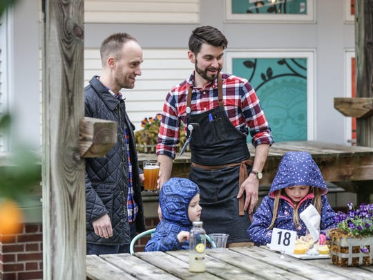 Director of Hospitality for the Indianapolis Museum of Art, Josh Ratliff, right, serves up beer, lemonade and pretzels to Ryan, left, Spencer, center, and Audrey Pettibone, right, during opening day at the Spring Blooms  Beer Garden, March 31, 2017.