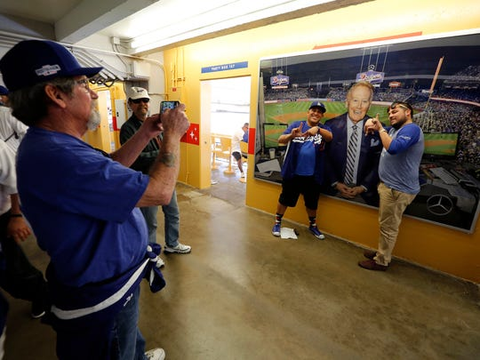 Baseball fans pose for a picture in front of a photo of Vin Scully before the start of an opening day game between the Dodgers and the San Diego Padres on Monday at Dodger Stadium.