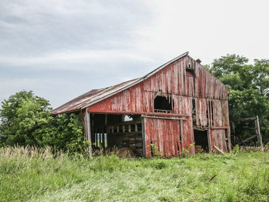 An old barn sits in a field where it's in the process