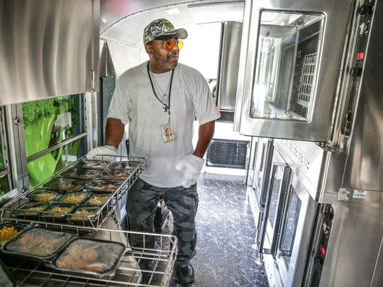 Bus driver and food service worker Clarence Washington pulls corn and breaded chicken nuggets from the oven inside the Indianapolis Public Schools Bus Stop Cafe during a visit to the Stratford Apartments Complex in Indianapolis on Friday, July 21, 2017. The cafe brings meals to children during summer break.