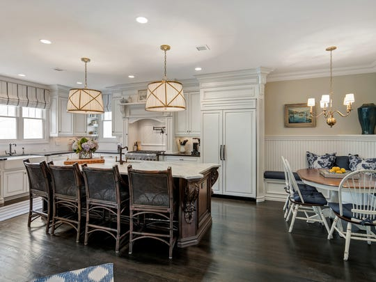 Gourmet kitchen with rich custom cabinetry, an oversized center island .