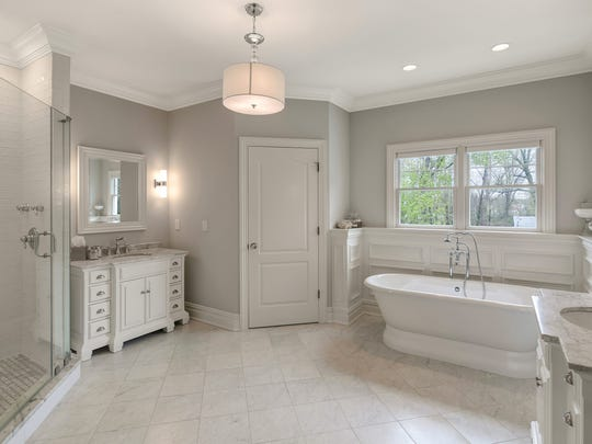 The luxurious master bathroom retreat features an expansive his/her spa-like bath, with custom vanities, and marble designer tile.