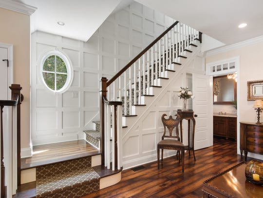 A grand staircase with spectacular millwork, hinting