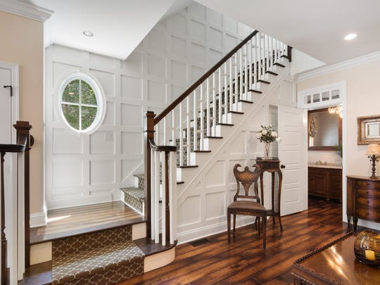 A grand staircase with spectacular millwork, hinting at the custom finishes throughout the home.