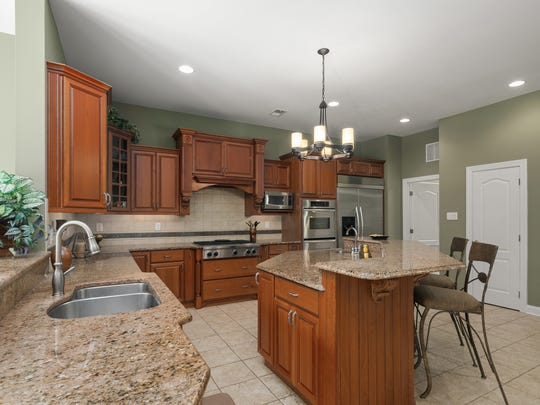 The gourmet kitchen features a center island, ceramic tile flooring and granite counter tops.