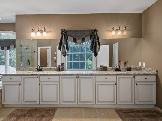 Master Bath offers a ceramic tile flooring, shower stall, and  whirlpool.