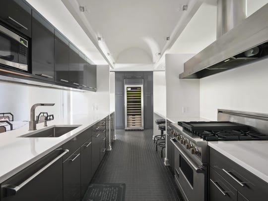 Kitchen features customized tile flooring and white