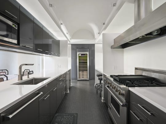 Kitchen features customized tile flooring and white stone countertops.