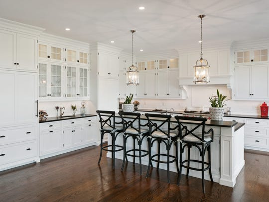 All white kitchen features the refrigerator covered in a wooden panel and huge center island.