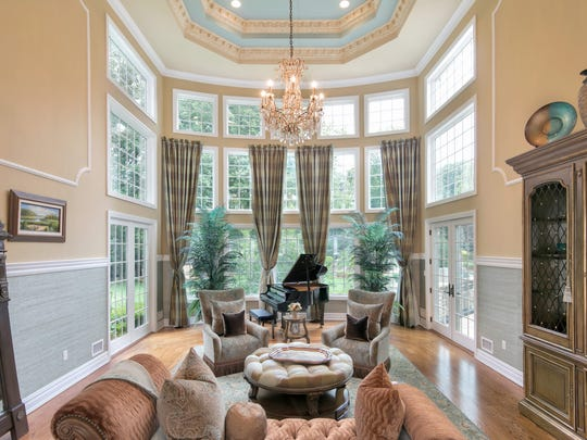 Magnificent oversized windows and multiple sets of customized French door are featured in the living room.