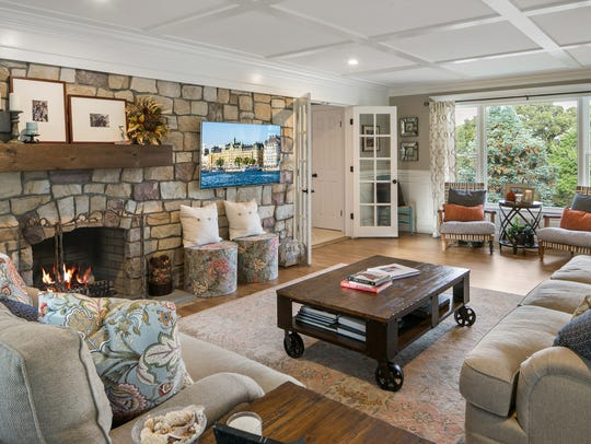 The stone wall features a built-in fireplace and bay windows.