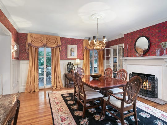 The grand dining room features customized decorative molding and a set of sliders.