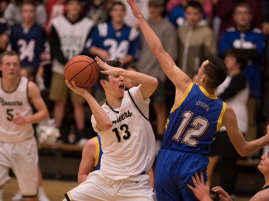 Boonville's Rylan Hicks (13) shoots while being guarded by Castle's Alex Hemenway (12) at Boonville High School Tuesday night. The Knights beat the Pioneers 77-60.