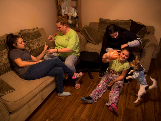 Jizel Diaz, 15, left, has her nails done by mom, Jacqueline Linares of Owensboro, Ky., as her sister, Graciela Citlahua, 14, braids her 10-year-old cousin, Cecily Cuahua's, hair Tuesday night. Cecily Cuahua, 10, her brother, Enrique, 5, and sister, Marrissiah, 6, are staying at their Aunt Jacqueline's house until they can obtain passports and move to Mexico, a country they've never visited, to live with their father, Antonio Cuahua, who was deported after a U.S. Immigration and Customs Enforcement (ICE) raid recently.