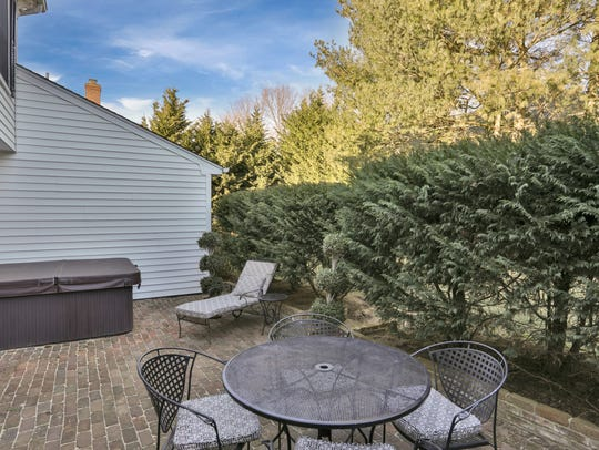 The backyard offers a stone paved patio a hot tub surrounded by tall trees for privacy.