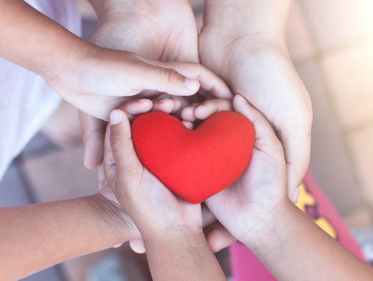 Red heart in child and parent hands with love and harmony