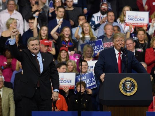 President Trump, with Rick Saccone, speaks to supporters at the Atlantic Aviation Hanger on March 10, 2018, in Moon Township, Pennsylvania. The president made a visit in a bid to gain support for Republican congressional candidate Rick Saccone.