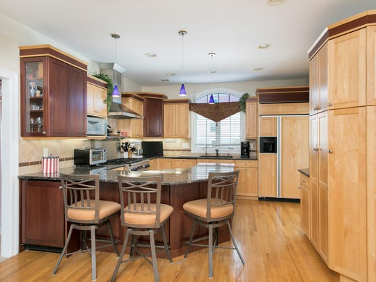 The kitchen features octagonal breakfast nook and a customized bookcase.