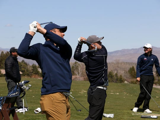 Nevada's Sam Meek, front, and Sam Harned, middle, hit balls on the range as the golf team practices at the Montreux Golf & Country Club last month.