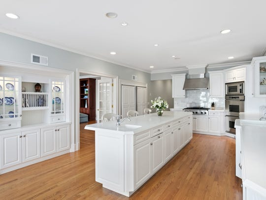 The all-white kitchen with custom cabinets and stainless appliances.