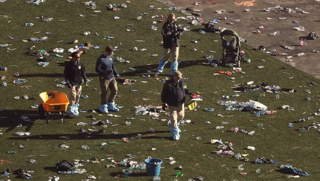 Investigators walk through debris on festival grounds across the street from the Mandalay Bay Resort and Casino on Tuesday, Oct. 3, 2017, in Las Vegas. Authorities said Stephen Craig Paddock broke windows on the casino and began firing with a cache of weapons, killing dozens and injuring hundreds at the festival. (AP Photo/Marcio Jose Sanchez)