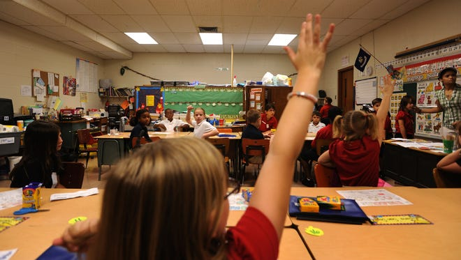 Students answer questions in an elementary school classroom.