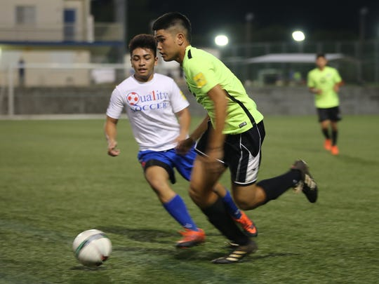 Bank of Guam Strykers' Joshua Calvo makes a run past Quality Distributors' Melvin Cristobal in the opening U18 division match of the Aloha Maid Minetgot Cup Elite Youth League at the Guam Football Association National Training Center played Aug. 21.