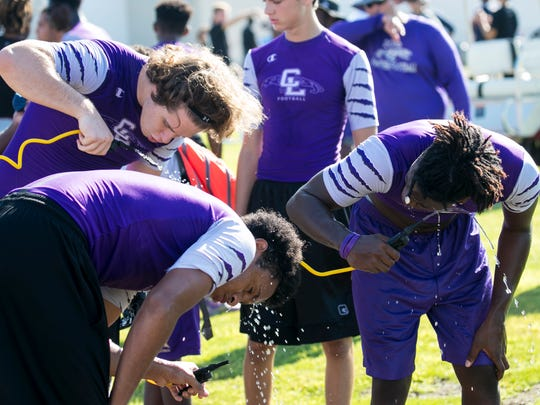 Cypress Lake High School football players get water and cool off during  a 7-on-7 football tournament at South Fort Myers High School on Wednesday.