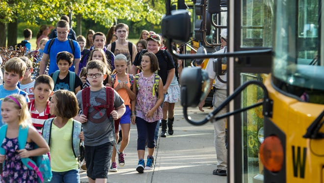Students get of of school buses on the first day of classes at the Williston Central School on Wednesday, August 26, 2015.