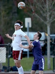 Kingston's Henry Golden heads the ball up the field.