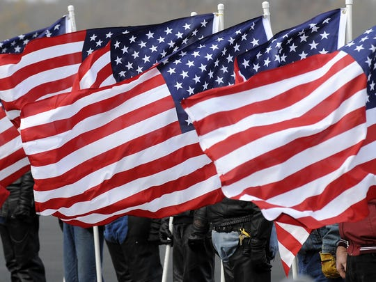 Members of the Patriot Guard Riders hold American flags during a military funeral on Nov. 20, 2008.