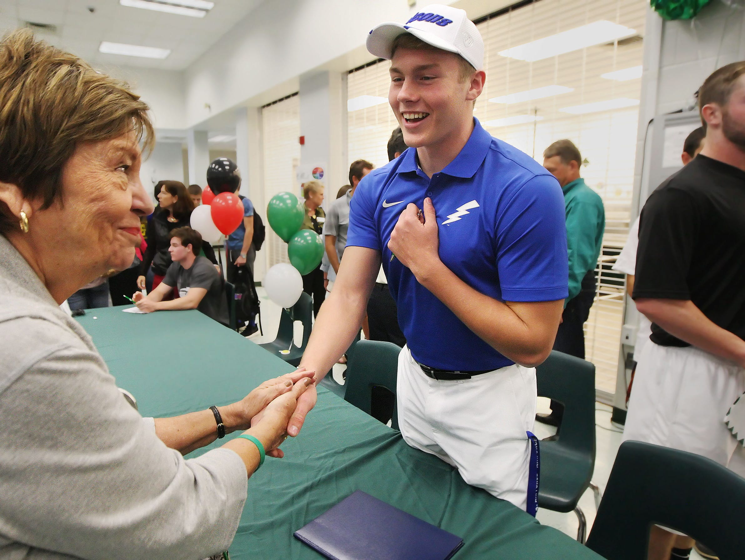 Margaret Sirianni, left, congratulates Fort Myers High School's Sam Turner after he signed a National Letter of Intent on Wednesday at Fort Myers High School. Turner signed to play football at the United States Air Force Academy.