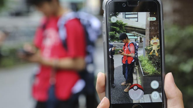 """In this file photo, a student plays """"Pokemon Go"""" in the street. A person playing in Hackettstown found $2,000 on the street."""
