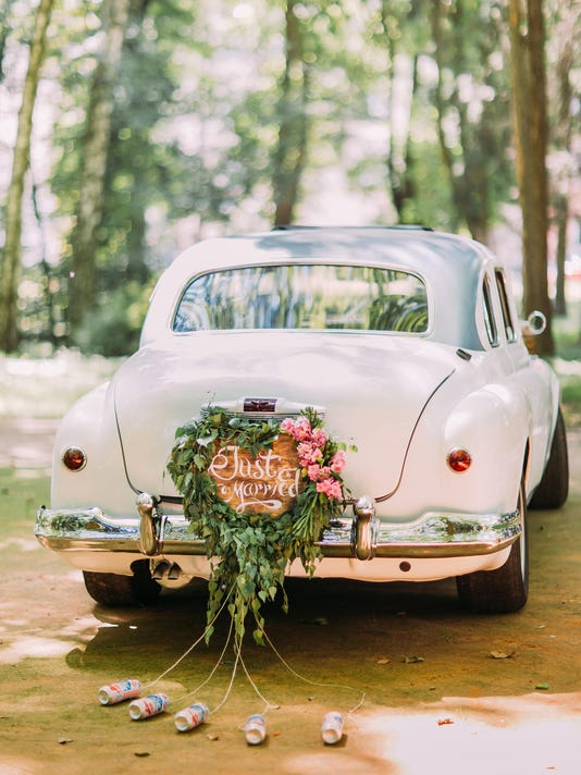 Bumper of retro car with just married sign and cans