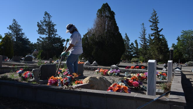 Robyn Delaney pitches in Saturday during a cleanup of Hillcrest Cemetery.
