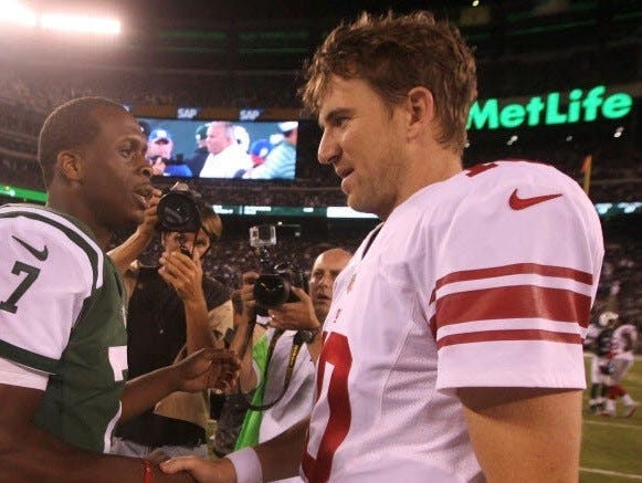 Former Jets quarterback Geno Smith, left, now a Giant, with Eli Manning.