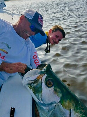 Capt. Ed Zyak of Local Color Guide Service in Jensen Beach helps to hold the tarpon caught and released by Jake Hester