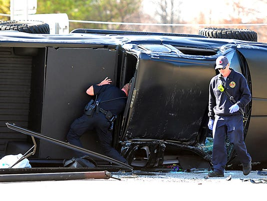 Police and fire officials examine Carolina Panthers quarterback Cam Newton's damaged truck following a crash in uptown Charlotte